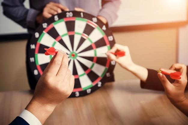 Squadra di affari che indica un dardi che mirano all'affare del centro di obiettivo, mirante al concetto di affari