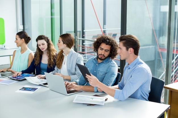 Squadra di affari che lavora al computer portatile e alla compressa digitale nella riunione