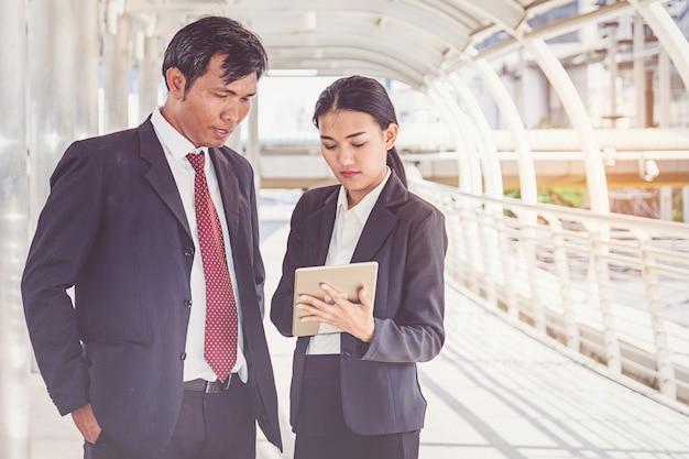 Squadra di affari che lavora in città, guardando un tablet