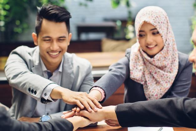 Squadra di affari che mostra insieme unità con le loro mani