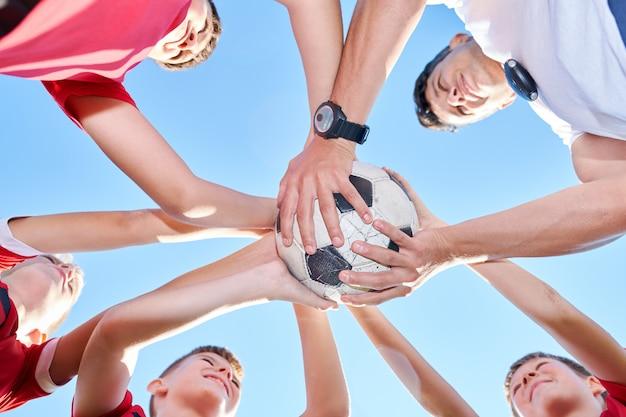 Squadra di calcio che si stringe attorno a ball
