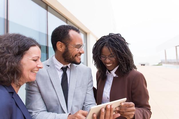 Squadra di colleghi multietnica emozionante felice che guarda video