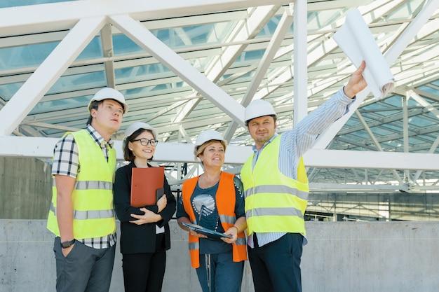 Squadra di costruttori ingegnere architetto sul tetto del cantiere.