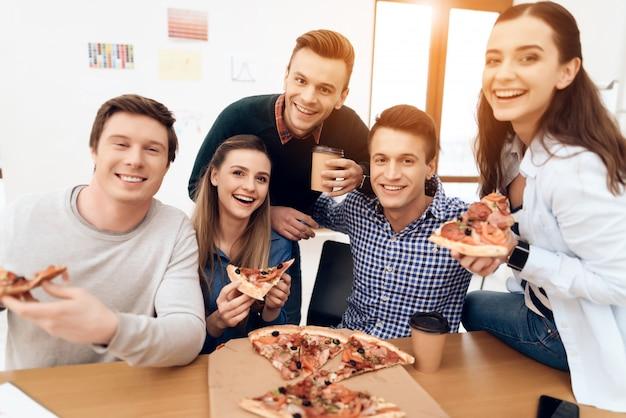 Squadra di giovani felici che mangiano pizza in pausa pranzo