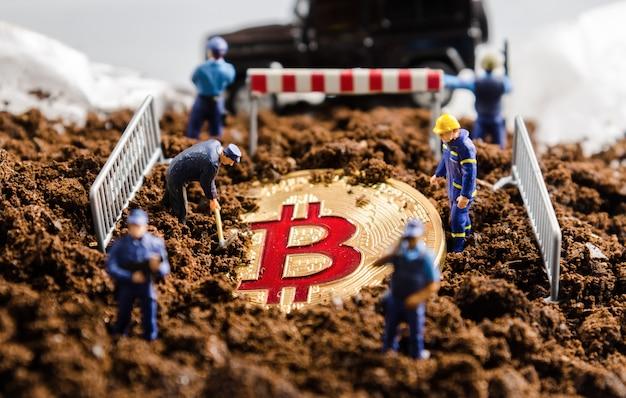 Squadra di minatori in miniatura che scava bitcoin d'oro