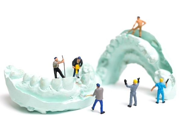 Squadra di operai in miniatura sta depositando denti finti