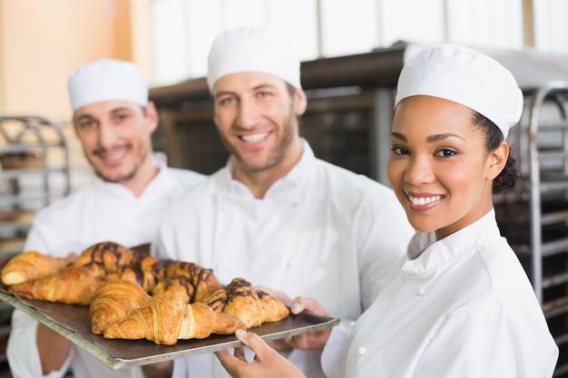 Squadra di panettieri che sorride alla macchina fotografica con vassoi di croissant