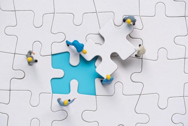 Squadra di persone in miniatura cercando di completare l'ultimo pezzo di puzzle