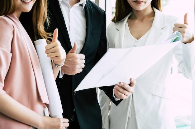 Squadra di tre amici di affari di fiducia con il pollice in su