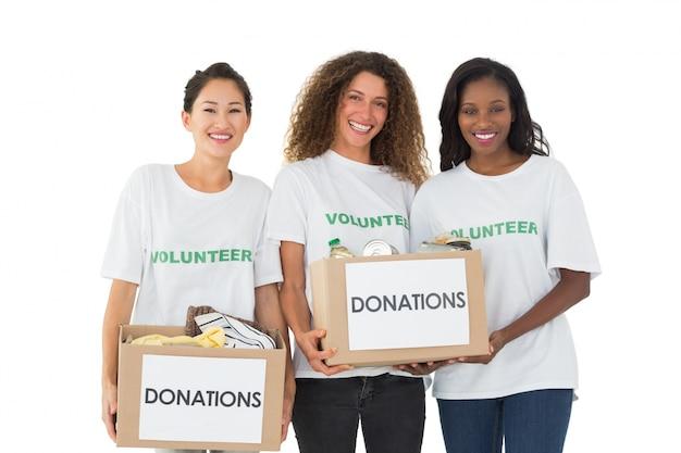 Squadra di volontari che sorridono alle caselle di donazioni della holding della macchina fotografica