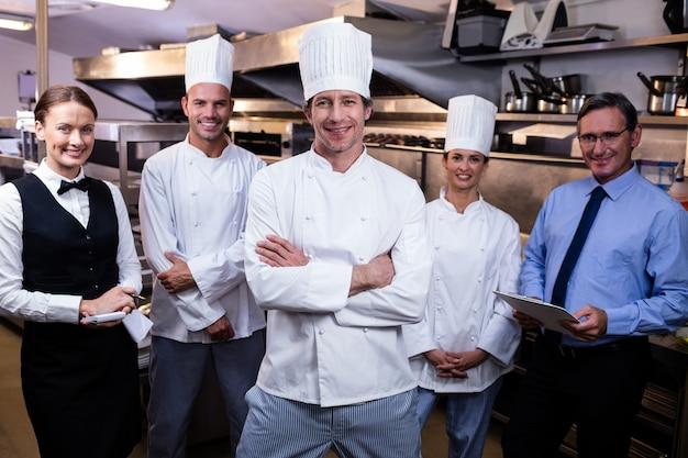 Squadra felice del ristorante che sta insieme nella cucina commerciale