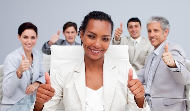 Squadra felice di affari che celebra un successo con i pollici su