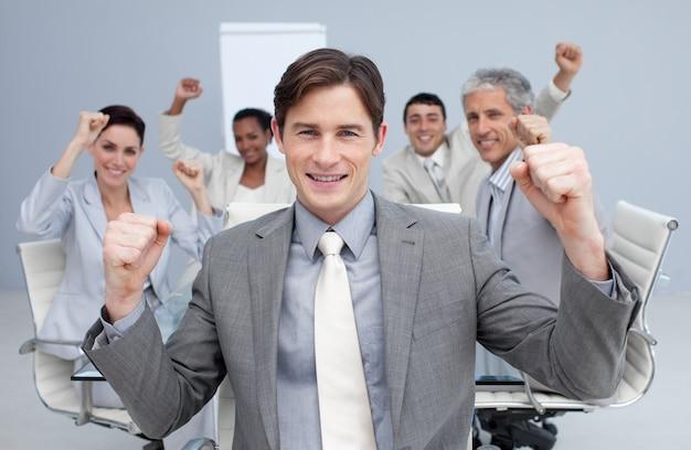 Squadra felice di affari che celebra un successo con le mani in su