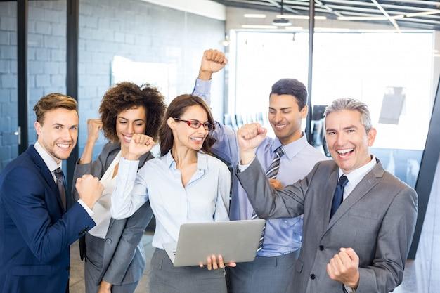 Squadra felice di affari che celebra un successo in ufficio