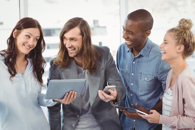 Squadra felice di affari che usando tecnologia mentre stando all'ufficio