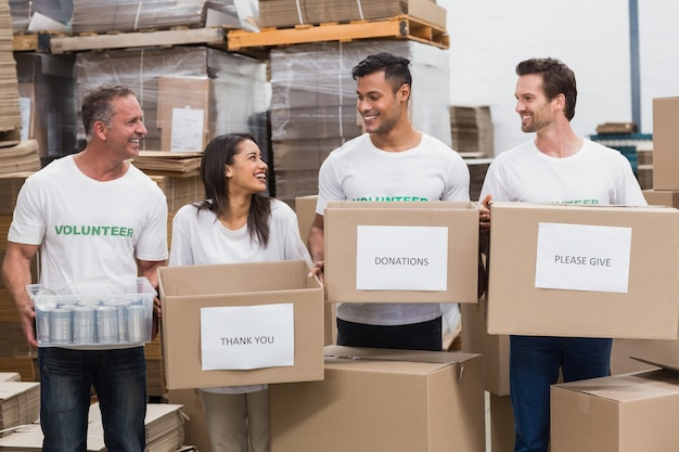 Squadra felice di volontari che tengono le scatole di donazioni