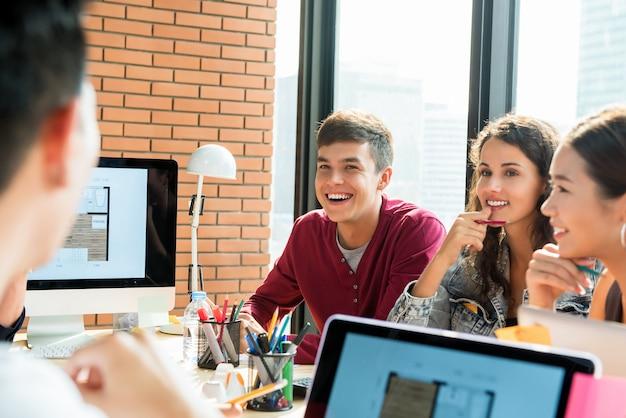 Squadra giovane architetto arredatore che sorride e che esamina il loro collega nella riunione