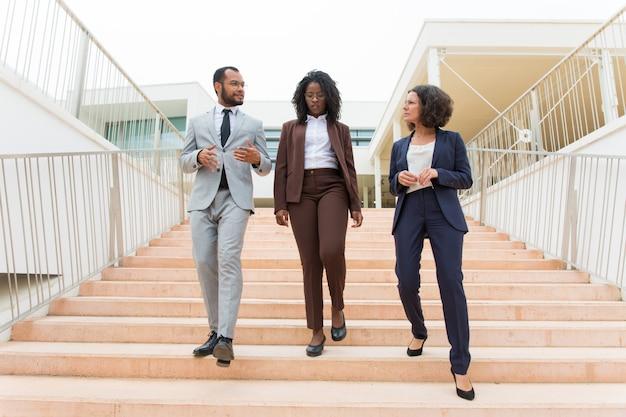 Squadra multietnica di affari che cammina di sotto