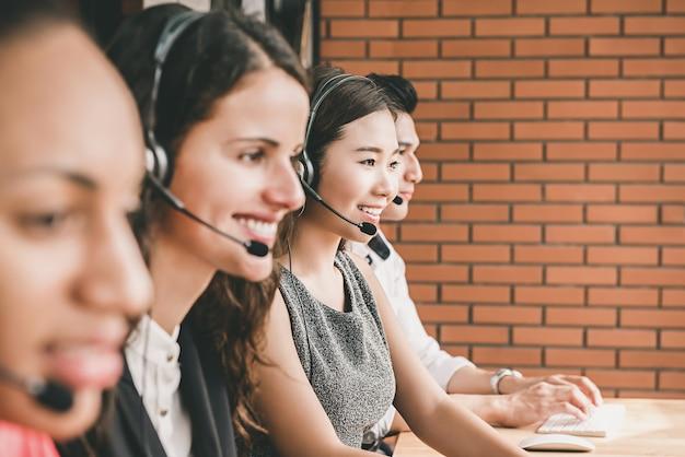 Squadra multietnica sorridente di servizio di assistenza al cliente di telemarketing che lavora nell'ufficio della call center