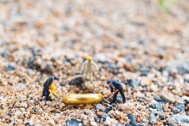 Squadra operaia scavando anelli d'oro sul pavimento