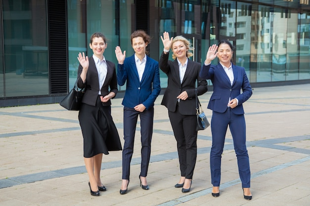 Squadra professionale femminile di successo felice che sta insieme vicino all'edificio per uffici, salutando, in posa, guardando la fotocamera e sorridente a figura intera, vista frontale. concetto di ritratto di gruppo di donne di affari