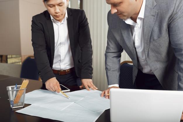 Squadra sicura di ingegneri che lavorano insieme in uno studio di architetto.