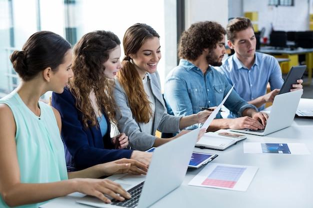 Squadra sorridente di affari che lavora al computer portatile e alla compressa digitale nella riunione