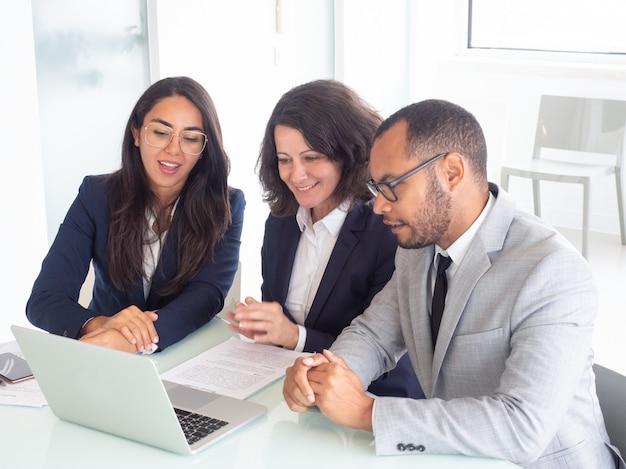 Squadra sorridente di affari che per mezzo del computer portatile
