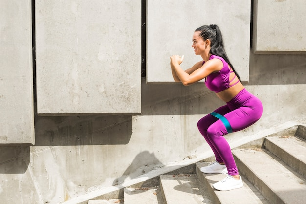 Squat. giovane donna sportiva della banda di resistenza che fa esercizio tozzo con la banda del bottino che allunga cinghia. la fitness femminile allena la gomma