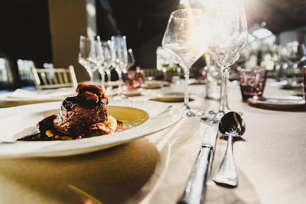 Squisita carne di vitello con salsa servita in posate di lusso con raggi di sole in un ristorante.