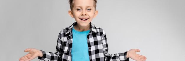 Sta un bel ragazzo in camicia a quadri, camicia blu e jeans. il ragazzo allargò le mani in entrambe le direzioni