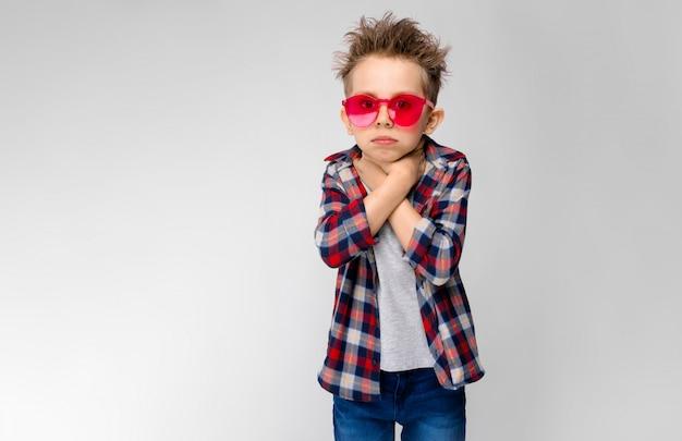 Sta un bel ragazzo in camicia a quadri, camicia grigia e jeans. un ragazzo in occhiali da sole rossi. il ragazzo si tiene le mani in gola.