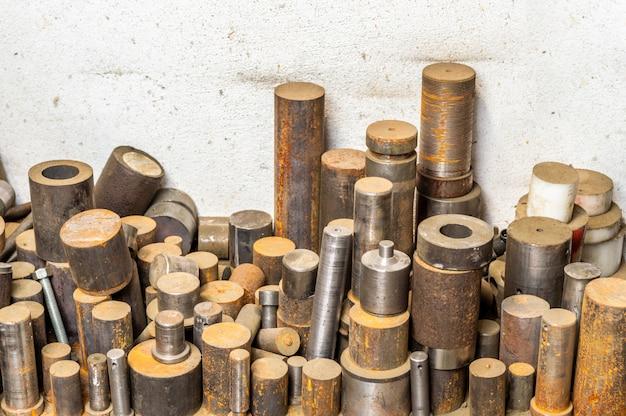 Stack di barre metalliche tornite sul pavimento della fabbrica