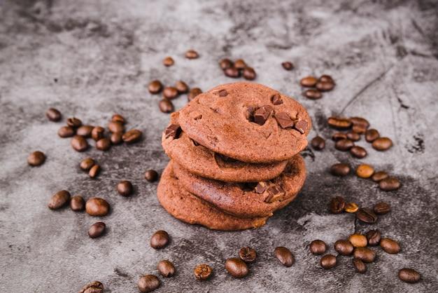 Stack di biscotti circondato con chicchi di caffè tostato
