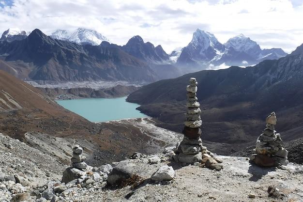 Stack di pietra sulla montagna più alta di gokyo ri nella rotta vertice del campo base dell'everest con il lago gokyo turchese nel percorso di trekking a khumbu, nepal