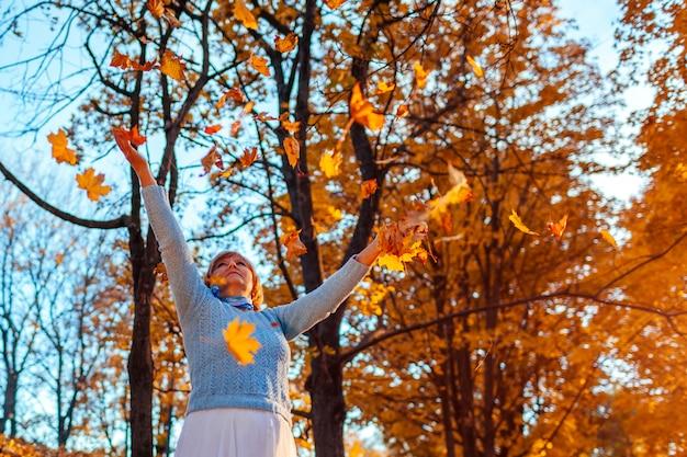 Stagione autunnale. foglie di lancio della donna nella foresta di autunno. donna senior divertendosi all'aperto