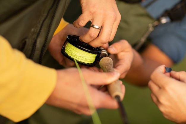 Stagione di pesca. chiuda in su della mano del pescatore con la filatura