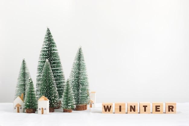 Stagione invernale, casa bianca miniatura con il pino e lettera sui blocchetti di alfabeto di legno con copyspace