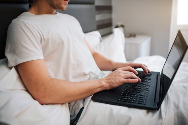 Stamattina ha tagliato la vista del giovane a letto. lavora tenendo il portatile e digitando sulla tastiera. lavoro da casa. daylight.