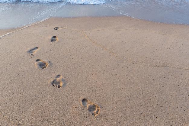 Stampa del piede nella sabbia sullo sfondo spiaggia