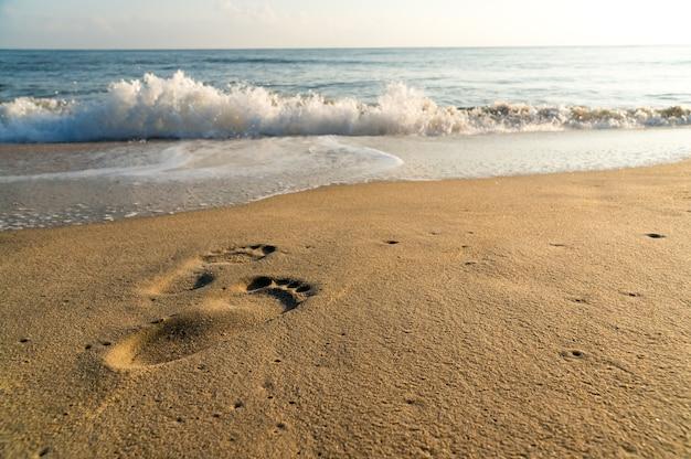 Stampa del piede umano sulla spiaggia con piccole onde e cielo blu