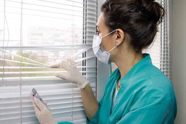 Stanco medico donna italiana in maschera medica, guanti e tuta medica guarda pensieroso fuori dalla finestra