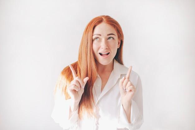 Stand di donna dai capelli rossi isolato su uno sfondo bianco in ampie camicie di grandi dimensioni. ragazza punta verso l'alto con il dito indice.