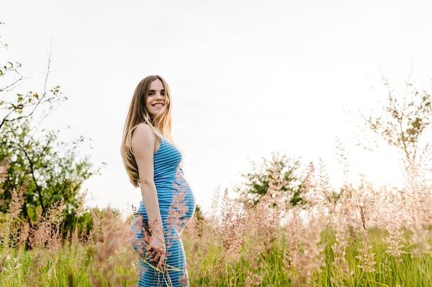 Stand di ragazza felice incinta su sfondo erba outdoort. mezza lunghezza, metà superiore. stai indietro. avvicinamento. il vento soffia i capelli.