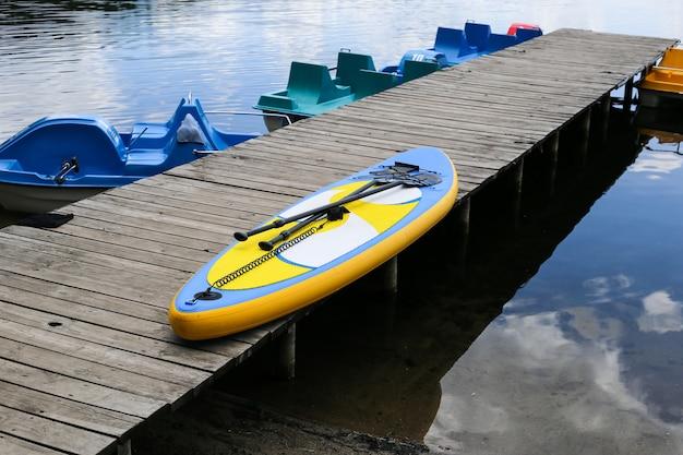 Stand up paddle board sul molo vicino al fiume. tavola sup, tavola sup gonfiabile