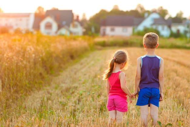 Standind del ragazzo e della bambina sul campo con luce solare dorata