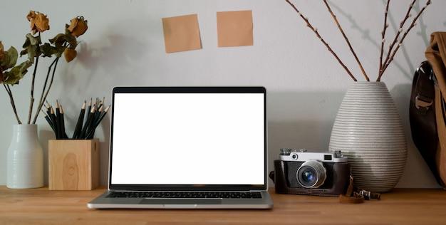 Stanza dell'ufficio del fotografo con il computer portatile dello schermo in bianco, gli articoli per ufficio e la macchina fotografica