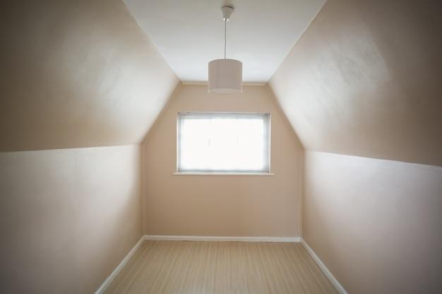 Stanza mansarda vuota in crema e beige
