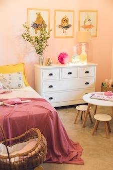 Stanza rosa delle ragazze rustiche con una carrozzina del giocattolo, un tavolo da disegno e le immagini degli animali