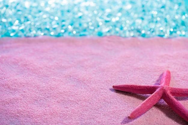 Starfish in spiaggia di sabbia rosa e mare tropicale